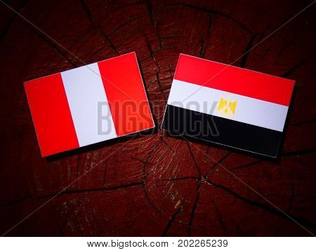Peruvian Flag With Egyptian Flag On A Tree Stump Isolated