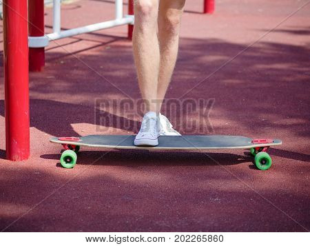 Close-up picture of young man's legs in white sneakers standing on a long, gray skateboard on a bright blurred park background. Trendy, extreme and dynamic modern youth activities and sports.