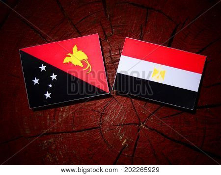 Papua New Guinea Flag With Egyptian Flag On A Tree Stump Isolated