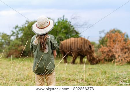 Back view of a little girl on safari walking close to  white rhino
