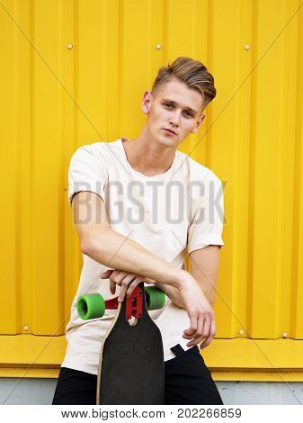 Portrait of a beautiful, confident, serious teen in a white shirt and black trousers. A handsome, stylish hipster dude with a modern skateboard sitting on a saturated yellow background.
