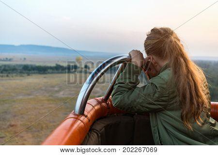 Little girl enjoying early morning flight on hot balloon in Masai Mara national park, Kenya