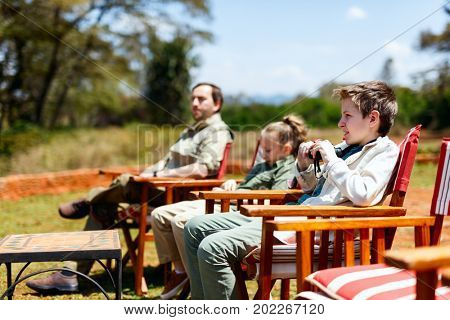 Family of father and kids on African safari vacation enjoying wildlife viewing