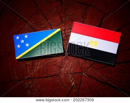 Solomon Islands Flag With Egyptian Flag On A Tree Stump Isolated