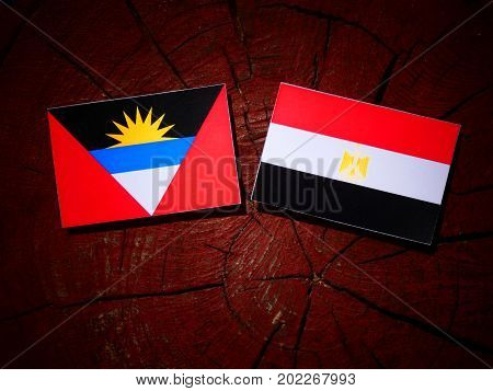 Antigua And Barbuda Flag With Egyptian Flag On A Tree Stump Isolated