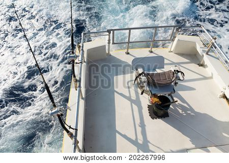 View from upper bridge of deep sea sport fishing boat with 2 lines set up and empty fish fighting chair. Offshore fishing in Hawaii.
