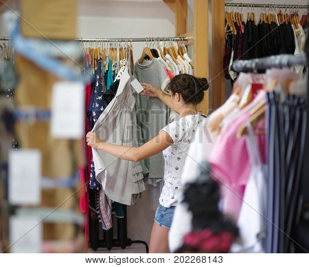A portrait of a young woman on a blurred background. A emale choosing herself a beautiful stylish dress in a clothing store and looking at a price. Shopping, consumerism concept. Copy space.