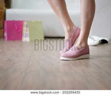 A close-up picture of female's legs wearing a pair of casual light pink shoes on a shop background. Stylish and trendy woman's boots on feet. Glamorous girl choosing shoes in a shop. Fashion concept.