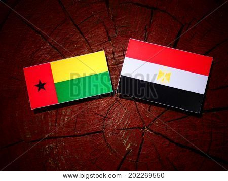 Guinea Bissau Flag With Egyptian Flag On A Tree Stump Isolated