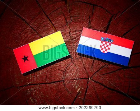 Guinea Bissau Flag With Croatian Flag On A Tree Stump Isolated