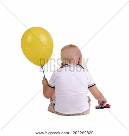A full-length portrait of a small blond boy turned back playing with a big bright yellow balloon. A kid with a balloon. A cute child isolated on a white background. Chilhood concept.