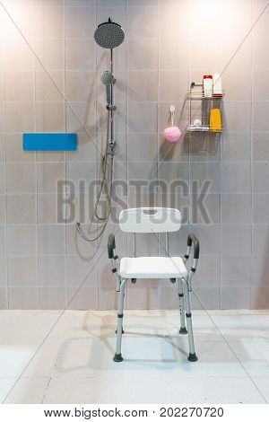 Padded Shower Chair With Arms And Back In Bathroom With Bright Tile Wall And Floor.