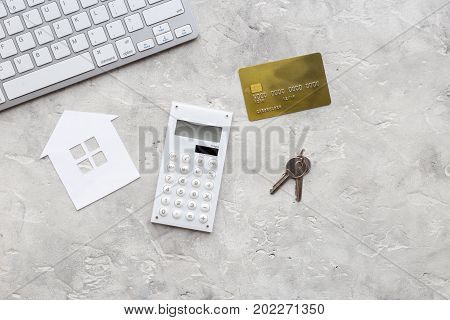 purchasing house set with online credit card payment on work desk stone background top view