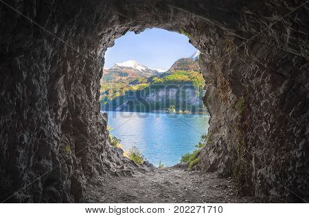 Cavern at the end of a tunnel with stone walls and a lovely view over the Swiss Alps and the Walensee lake.