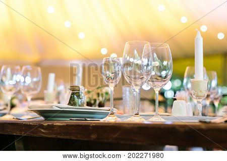 dining, entertainment, night life concept. three transparent glasses of streamlined forms standing on the wooden table in vintage style with full complect of silverware