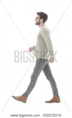 Side view.Young smiling man walking forward