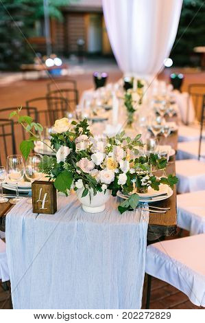 flower arrangement, design, spring concept. table numbered four decorated with help of florist that created stunning bouquet composed of avalanches and such verdure as brunch of raspberry and rosebush