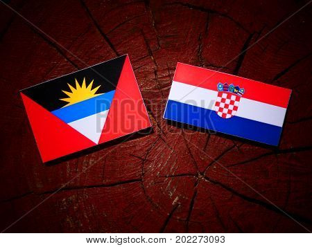Antigua And Barbuda Flag With Croatian Flag On A Tree Stump Isolated