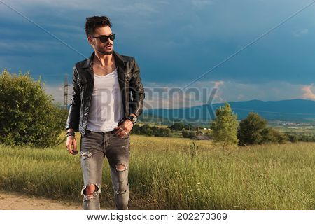 young sexy man walking on the side of a country road near a grass field and looks to side