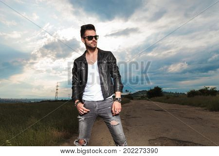 fashion man in leather jacket and sunglasses standing in the middle of the road against sunny and cloudy sky