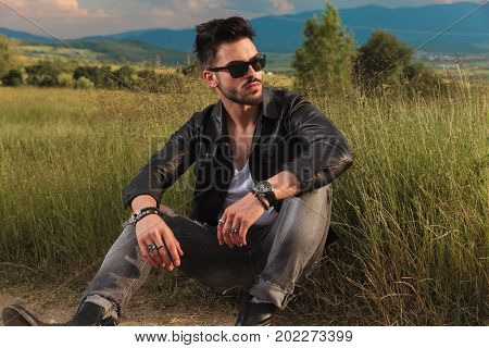 fashion man in leather jacket resting on the side of the road in nature