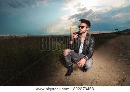 side view of a man smoking cigarette and looks away in the middle of a road