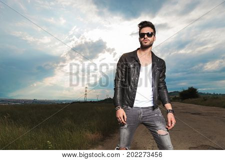 fashion model posing in the middle of nature on the side of a country road