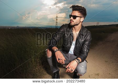 side view of a man in leather jacket and sunglasses holding cigarette on the side of a country road