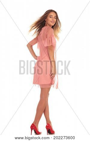 back view of a laughing woman in dress turning to the camera on white background