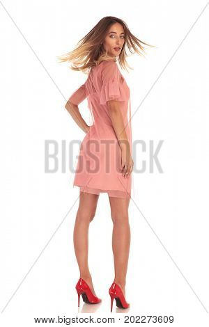 back view of a sexy woman in dress turning to the camera on white background