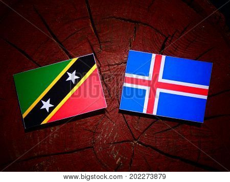 Saint Kitts And Nevis Flag With Icelandic Flag On A Tree Stump Isolated