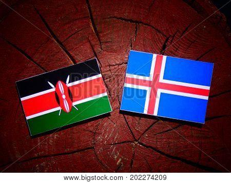 Kenyan Flag With Icelandic Flag On A Tree Stump Isolated