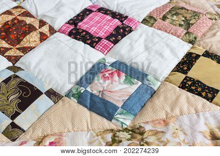 hobby, quilt, art concept. close up on piece quilt blanket patterned by a scattering of different geometrical figures such as triangles, squares and rhombuses