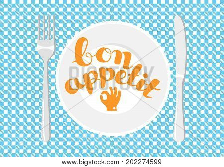 White plate on a checkered tablecloth. Lettering - Bon appetit
