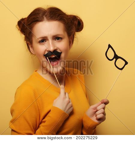 Young woman with  fake mustaches and glasses over yellow backgro