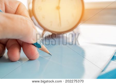 Alarm clock and optical form of standardized exams or test on touch screen tablet with hand holding blue pencil for examination Education conceptselective focusvintage