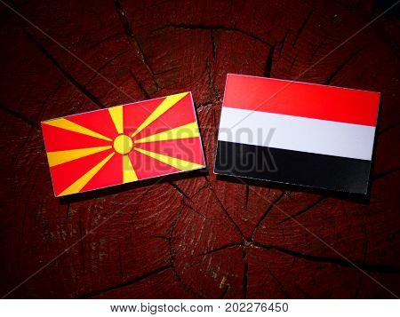 Macedonian Flag With Yemeni Flag On A Tree Stump Isolated
