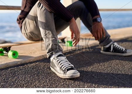 Anonymous man sitting on longboard after cruising along ocean promenade, fun active hobby outdoors activity