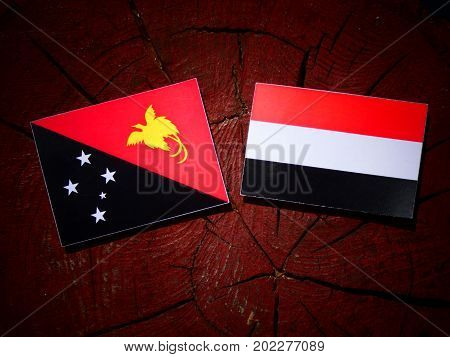 Papua New Guinea Flag With Yemeni Flag On A Tree Stump Isolated