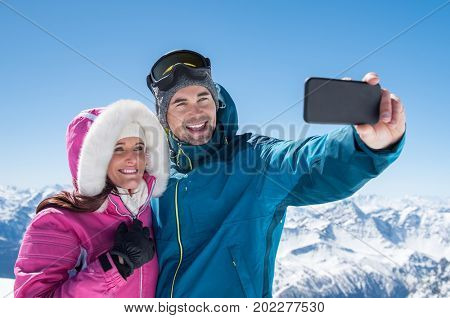 Happy couple taking selfie by smartphone over winter background. Man taking selfie with cheerful girfriend over snowy mountains. Beautiful couple enjoy winter holiday together.