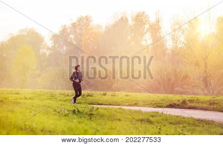 Young woman jogging in park at sunset. Young woman running in garden in a foggy day. Young fit woman keeping active by jogging in winter.