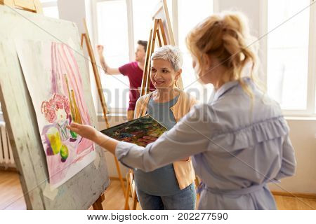 creativity, education and people concept - women artists discussing painting on easel at art school studio