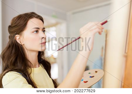 art school, creativity and people concept - student girl or young woman artist with easel, palette and paint brush painting at studio