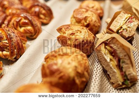 food, cooking and baking concept - close up of bread, buns, pies and sandwiches at bakery