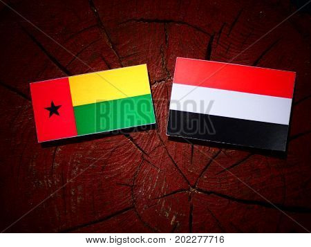 Guinea Bissau Flag With Yemeni Flag On A Tree Stump Isolated