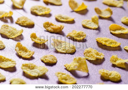 Row Corn flakes arranged on purple background, Breakfast or meal
