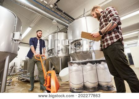 production, business and people concept - men with beer kegs on loader and clipboard working at craft brewery or non-alcoholic beverage plant