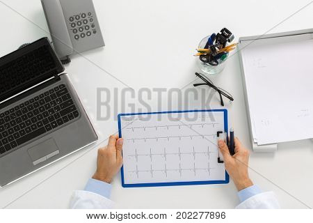 medicine, healthcare, cardiology and people concept - doctor hands with cardiogram on clipboard and laptop computer sitting at table in clinic