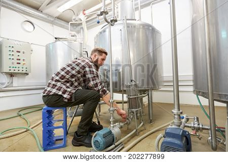 manufacture, business and people concept - men working at craft brewery or non-alcoholic beer production plant