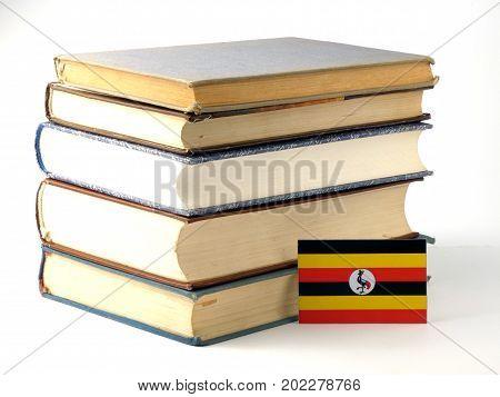 Uganda  flag with pile of books isolated on white background